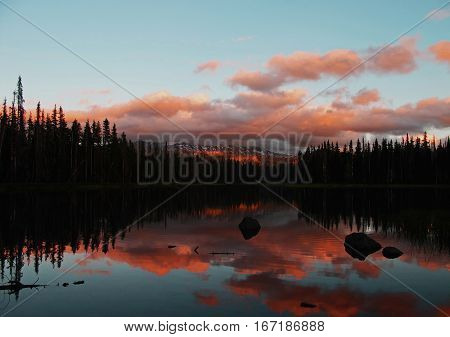The sun sets over Scott Lake in Oregon's Cascade Mountains and lights up the clouds with bright red colors and trees reflecting in the lake that is accented by boulders on a summer day.