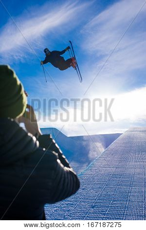 Photographer takes photo of halfpipe skier doing a grab trick
