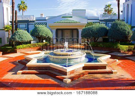 Spanish garden. Fountain. Plants. Blue sky. After rain.