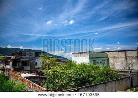 View of houses, mountains and building of brick slums in Bangu neighborhood, where the prison, the Penitentiary Complex of Gericino and Bangu dump are located, the West Zone of Rio de Janeiro, Brazil
