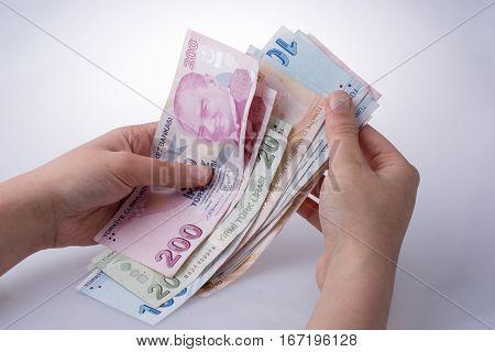 Hand holding Turksh Lira banknotes on white background