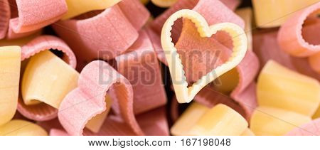 Red and yellow heart shaped pasta top view food background