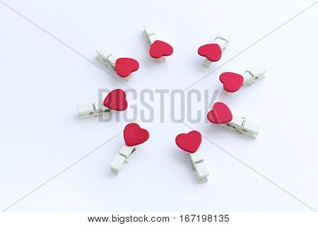 wooden clothes pin or cloth pegs with heart shape design for valentine on a white background