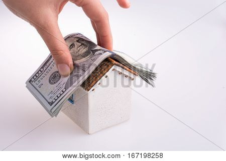 Hand Holding American Dollar Banknotes On The Roof Of A Model House