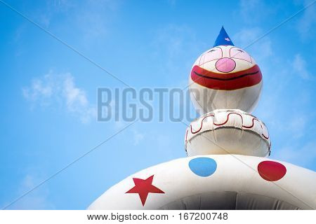 White clown jumping castle against blue sky background with white clouds