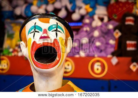 Sideshow clown game close up of single clown with prizes in blurred background