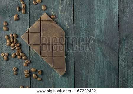 Artisan chocolate with coffee grains on a dark wooden boards texture, with copy space