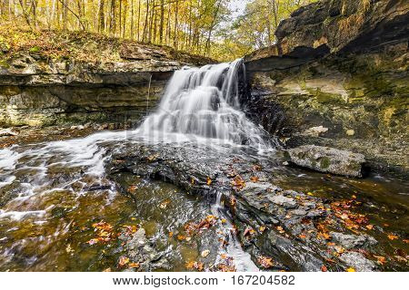 Whitewater cascades through an autumn landscape at McCormick's Creek Falls a waterfall in rural Owen County Indiana.