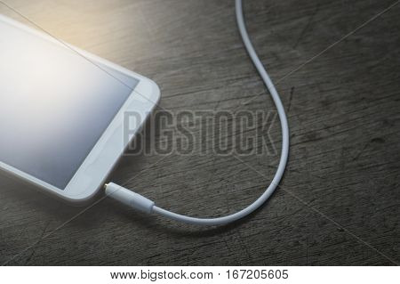 phone media portable and smart phone on dark tone. earphones and smartphone on wood table selective focus of earphones.