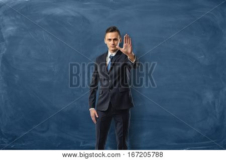 Businessman on blue chalkboard background holding one hand in a stop sign. Business communication. Leadership. Instructions.