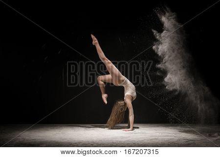 Slender girl dancing in cloud of white dust doing handstand studio shot