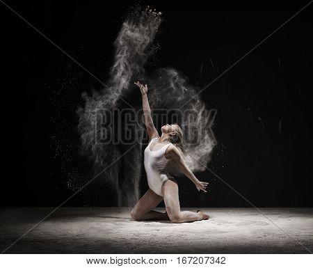 Woman in beige body posing in cloud of white dust streching gracefully up