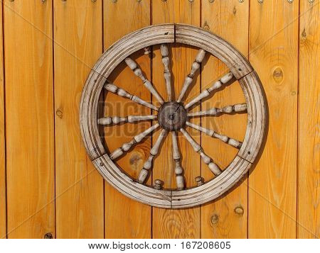 The improvised cart wheel against the background of gate from boards