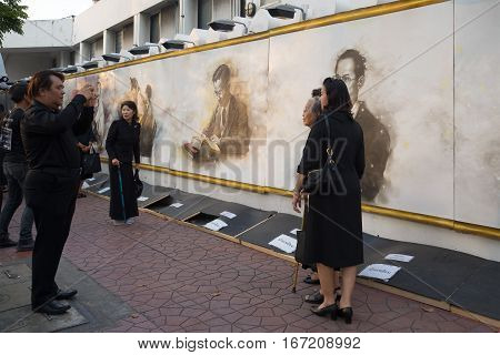 BANGKOK, THAILAND - DECEMBER 11, 2016: Thais in black mourning clothes are photographed at a wall with the image of the dead king Bhumibol Adulyadej. A fragment of funeral ceremonies in Bangkok