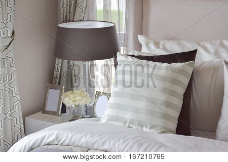 Modern Bedroom Interior With Green Striped Pillow On Bed And Bedside Table Lamp At Home