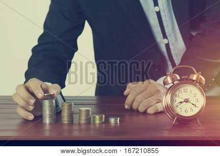 business man put money on pile of coins with alarm clock on working table concept in time to success