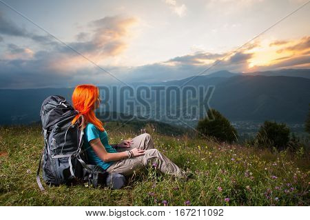 Red-haired Lady With Backpack In The Mountains At Sunset