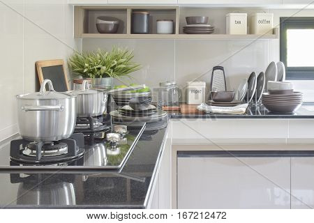 Stainless Pots And Ceramic Ware Setting On The Counter In The Kitchen