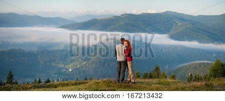 Romantic Couple Enjoying A Morning Haze Over The Mountains