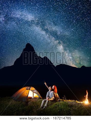 Romantic Couple Hikers Looking At The Shines Starry Sky At Night. Happy Pair Sitting Near Camp And C