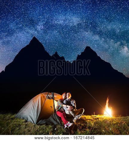 Two Hikers Having A Rest In His Camp At Night Near Campfire Under Shines Starry Sky