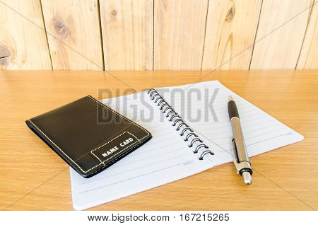 Card Holder,pen and notebook on wood table