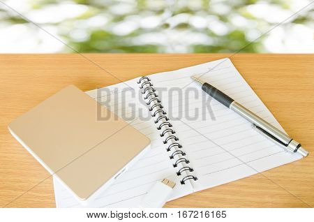 external hard drive for backup and storage data,notebook and pen on wood table with natural background