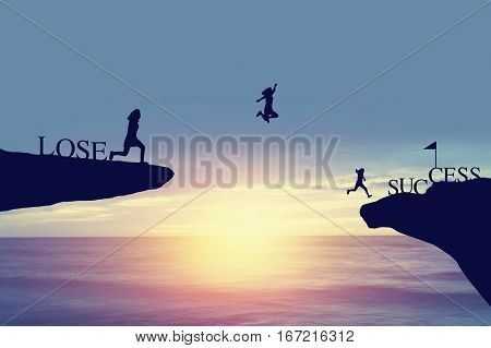 Silhouette of people jumping from lose side on rock to success and celebrat in business fiance and life
