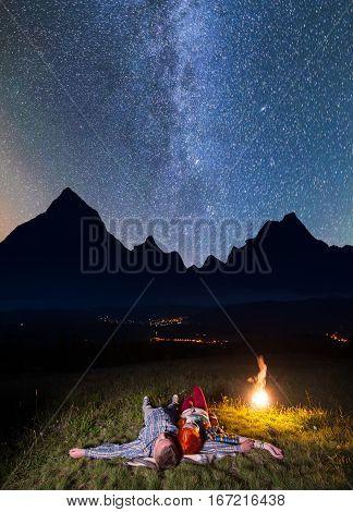 Romantic Couple - Girl And Guy Lying Near The Fire, Enjoying Incredibly Beautiful Starry Sky. Long E