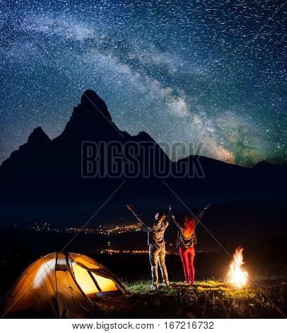Young Backpackers - Guy And Girl Raised Their Hands Up Under The Beautiful Starry Sky Near Campfire