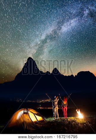 Happy Couple Hikers Raised Their Hands Up Under The Stars And Milky Way Near Bonfire And Tent