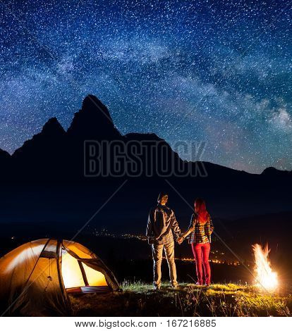 Night Camping. Romantic Couple Holding Hands, Standing Near Camp And Enjoying Starry Sky And Milky W
