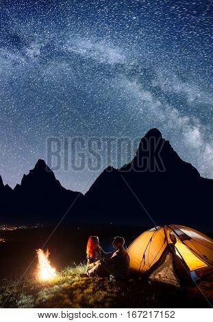 Loving Pair - Guy And Girl Sitting Face To Face In Front Tent Near Bonfire Under Shines Starry Sky A