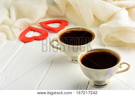 Two cups of morning fragrant coffee on St. Valentine's Day against the background of two red hearts and a white scarf