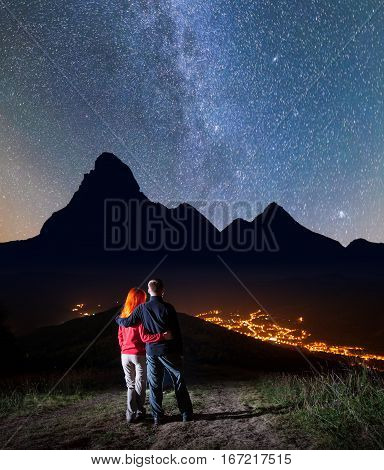 Romantic Couple - Girl And Guy Embracing Each Other, Standing On A Hill Under The Bright Stars And M