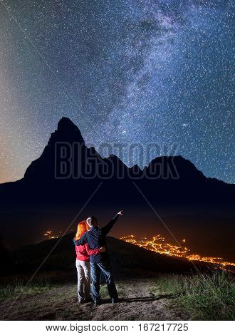 Romantic Couple - Girl And Guy Embracing. Man Showing On Stars And Milky Way In Beautiful Starry Sky