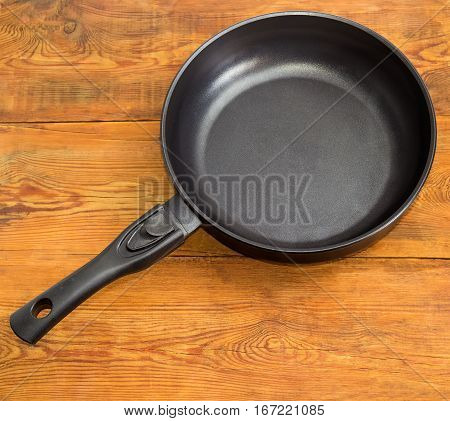 Modern cast frying pan made of aluminum alloy with ceramic non-stick coating and removable handle on an old wooden surface