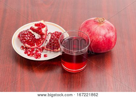 Pomegranate juice in a glass one ripe whole pomegranate part of the fresh split pomegranate on a saucer on a red wooden surface