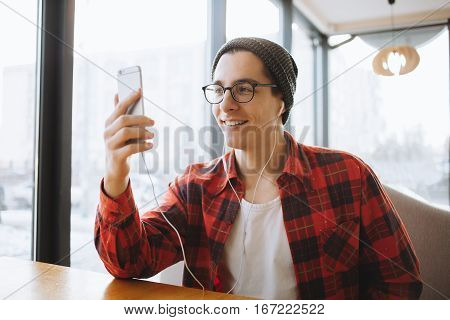 Attractive young man or freelancer is sitting in cafe near window in hat and eyeglasses during the coffee break. Handsome guy is smiling and talking with friends on skype
