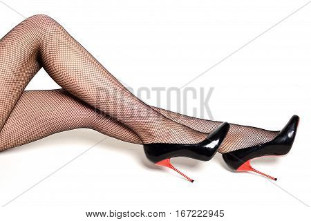 Sexy Female Legs In High Heel Shoes And Fishnet Stockings.