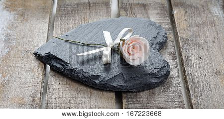 Stone heart and rose on old wooden background