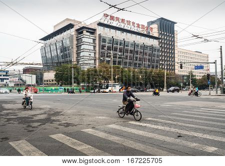 Beijing, China - Oct 30, 2016: Bikes traversing intersection at the 700-year-old Wangfujing Street crossing. Dongsi West Street is at right; Meishuguan East Street is to the left. Ahead is the Civil Aviation of China building.
