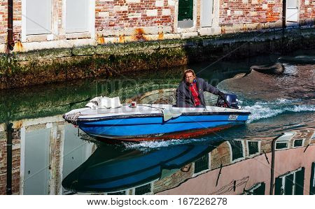 VeniceItaly July 28th2011: A man sailing a motor boat on a small canall in Venice Italy. Venice is a special city in Italybuilt in an archipelago of many islands formed by canals in a shallow lagoon connected by bridges. In the old centre the canals serve