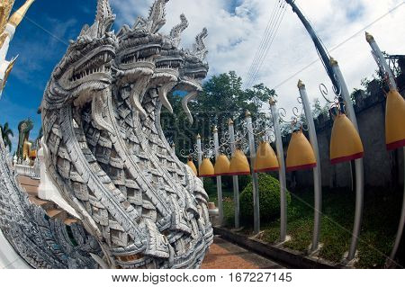 UBON RATCHATANI,THAILAND -JANUARY 17,2017 : Outdoor Serpent guardians and row of bell in Buddhism temple Wat Tham Khuha Sawan temple is located on a high cliff above the river Mekong Klong Chiam District, Ubon Ratchatani Province , Northeast Thailand.
