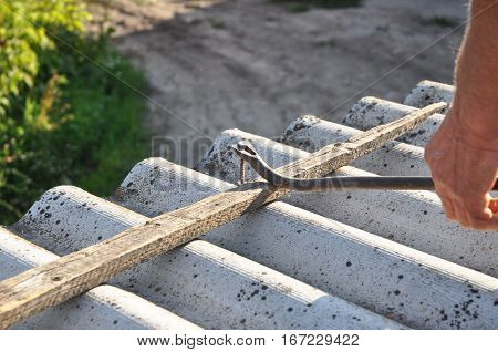Roof worker Roofer remove and repair dangerous asbestos old roof tiles. Roofing construction. Pull out the nails correctly from asbestos old roof tiles.