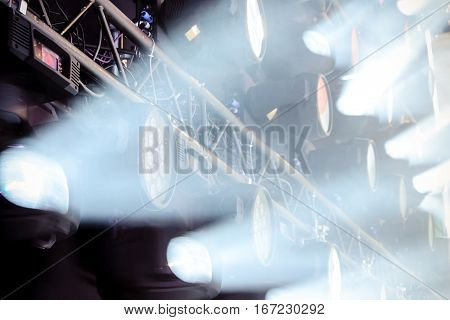 Stage lighting equipment. The direct rays of light in the haze.