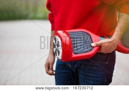 Guy holding modern red electric mini segway or hover board scooter in hands. Trending new transportation technology that produces no air pollution to the atmosphere. African male model close up on device