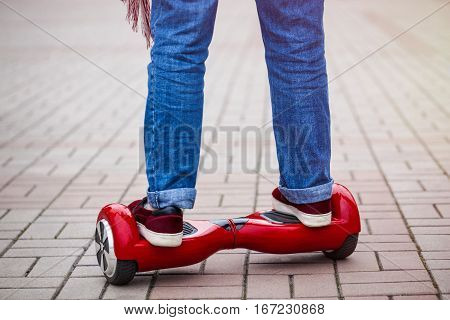 Feet of a girl riding on modern red electric mini segway or hover board scooter. Trending new transportation technology that is so much fun and easy to ride and produces no air pollution to the atmosphere. Close up on model legs and gadget.