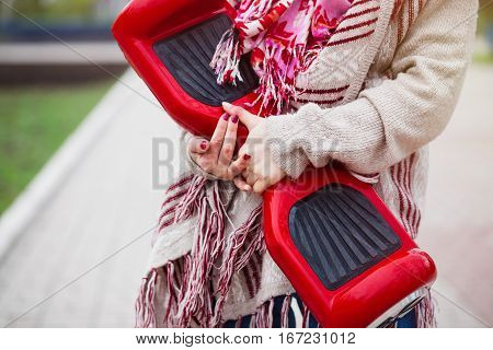 Female model holding modern red electric mini segway or hover board scooter in hands while walking in the park. Popular new transportation technology that produces no air pollution to the atmosphere. Girl is wearing trending boho style clothes.