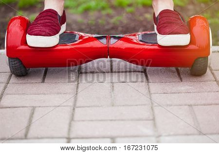 Cllose up on feet of a gir in marsala shoes riding on a modern red electric mini segway or hover board scooter. Trending new transportation technology that is so much fun and easy to ride and produces no air pollution to the atmosphere.